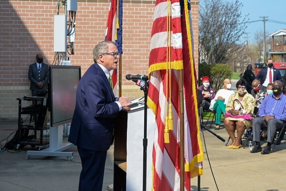 Governor Mike DeWine speaks from a podium outside Mayfair Elementary School in East Cleveland, Ohio, on Wednesday, April 7, 2021.